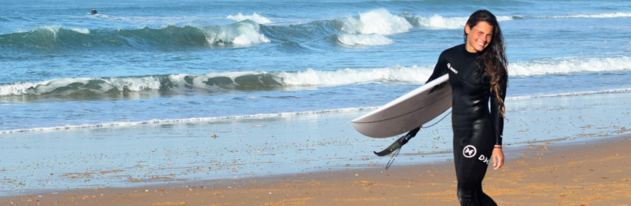Fabienne Sutter mit Surfboard am Strand