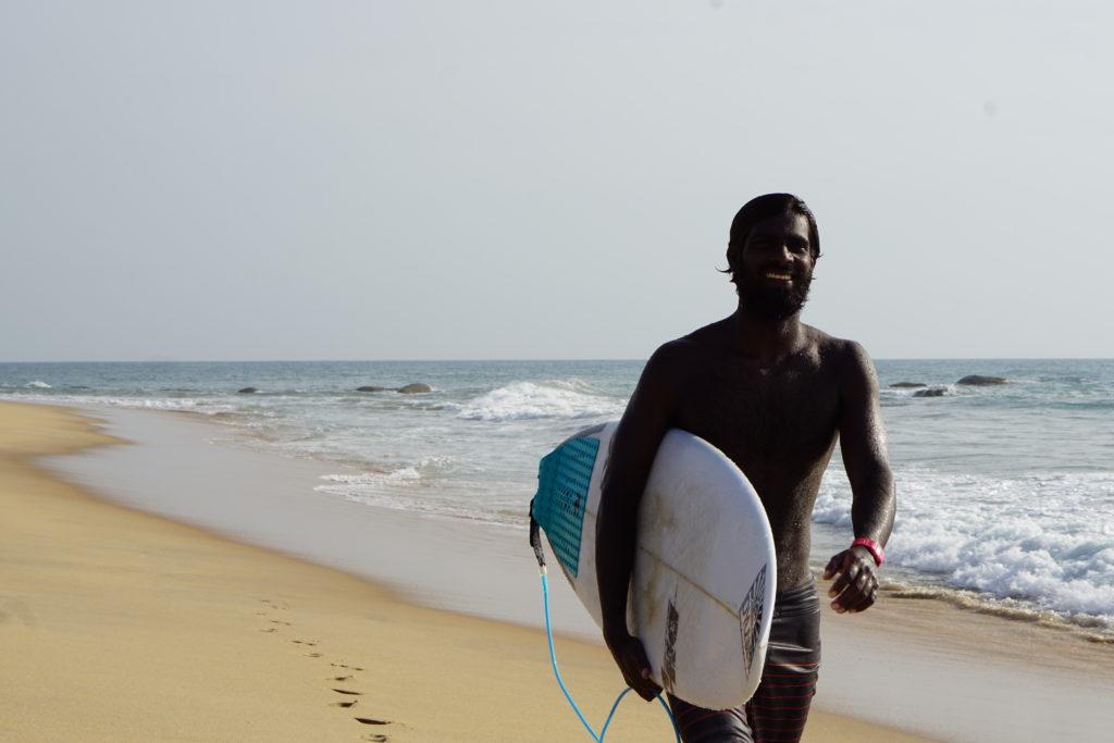 Dunkelhäutiger Surfer am Strand mit Brett
